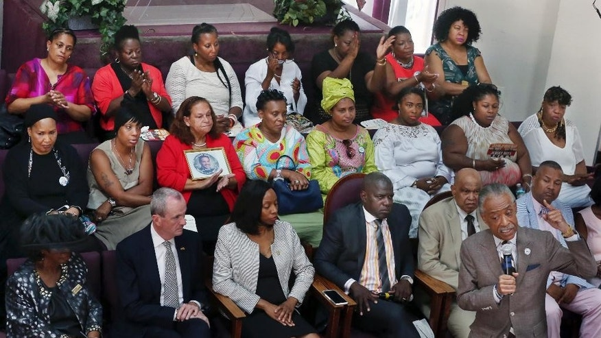 "Mothers of slain children fill the back two rows, including Gwen Carr, center right, mother of Eric Garner, as Rev. Al Sharpton, front right, speaks during services at Hope Memorial Baptist church Sunday, July 17, 2016, in Elizabeth, N.J. Two years after the chokehold death of Eric Garner made ""I can't breathe"" a rallying cry for protests over police killings of black men, federal authorities are still grappling with whether to prosecute the white officer seen on a widely watched video wrapping his arm around Garner's neck. (AP Photo/Mel Evans)"