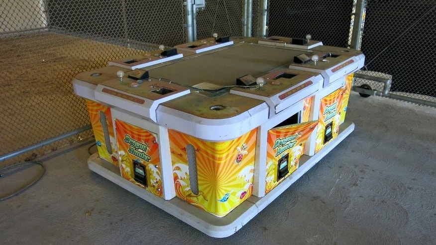 "This Friday, June 17, 2016, photo shows a six-seater arcade game seized by the Westminster Police during a raid of an illegal gambling house known as ""slaphouses,"" called so because of the sound players' hands make when hitting the machine controls in Westminster, Calif. Gambling has long been popular in the Vietnamese community that settled in Orange County after the fall of Saigon in 1975 and has since grown to 200,000. (AP Photo/Amy Taxin)"