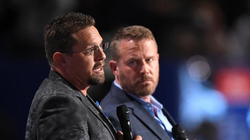 John Tiegen, a U.S. Marine Corp veteran, left, and Mark Geist, a U.S. Marine Corps veteran who fought in Benghazi, speak during the opening day of the Republican National Convention in Cleveland, Monday, July 18, 2016. . (AP Photo/Mark J. Terrill)