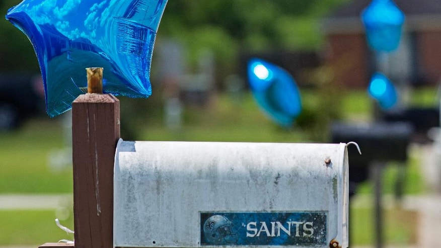 Balloons of support tied to mailboxes bounce in the wind across the street from the home of Baton Rouge Police officer Matthew Gerald in Denham Springs, La., Monday, July 18, 2016. Gerald was one of three law enforcement officers who were shot and killed Sunday. (AP Photo/Max Becherer)