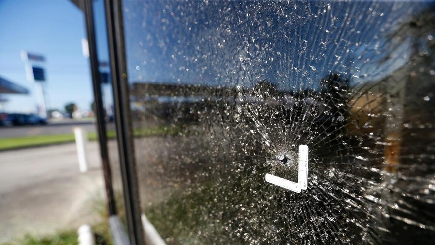 Shattered glass surrounds a bullet hole at Fitness Expo, Monday, July 18, 2016, at the fatal shooting scene in Baton Rouge, La., where several law enforcement officers were killed on Sunday. A former Marine set out to ambush police in Baton Rouge, authorities said Monday. (AP Photo/Gerald Herbert)