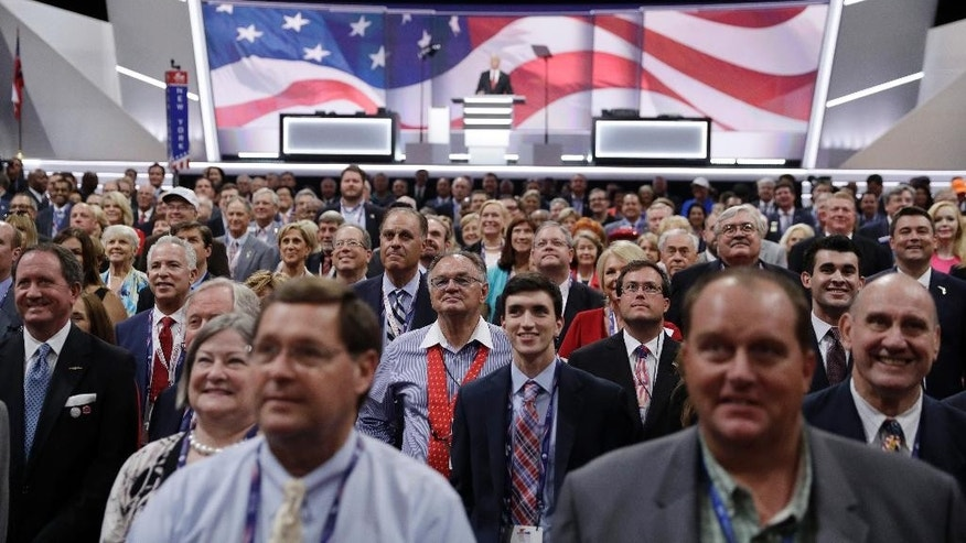 Delegates stand and turn toward the camera for the official photo during the opening day of the Republican National Convention in Cleveland, Monday, July 18, 2016. (AP Photo/John Locher)