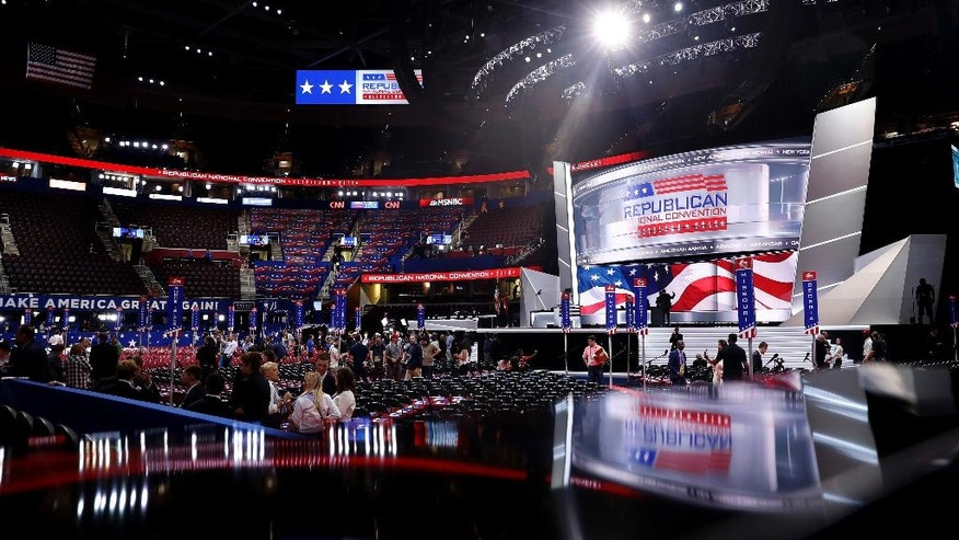 People walk on the floor before the start of the second day of the Republican National Convention in Cleveland, Tuesday, July 19, 2016. (AP Photo/Carolyn Kaster)