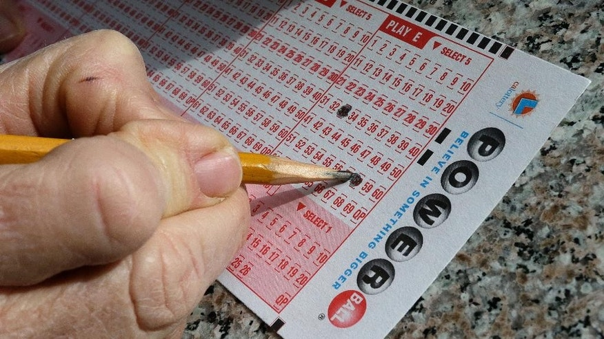 In this Jan. 12, 2016 file photo, a lottery player fills out numbers on a powerball form in Oakland, Calif.