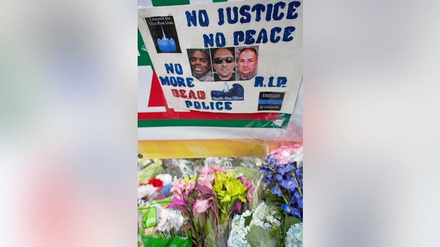 A memorial sign is posted Monday, July 18, 2016, in front of the B-Quick convenience store where law enforcement officers where engaged by a gunman and three were killed on Sunday in Baton Rouge, La. Pictured in the poster is, from left to right, Montreal Jackson, Matthew Gerald, both with the Baton Rouge Police Department and Brad Garafola of the East Baton Rouge Sheriff's Office. (AP Photo/Max Becherer)