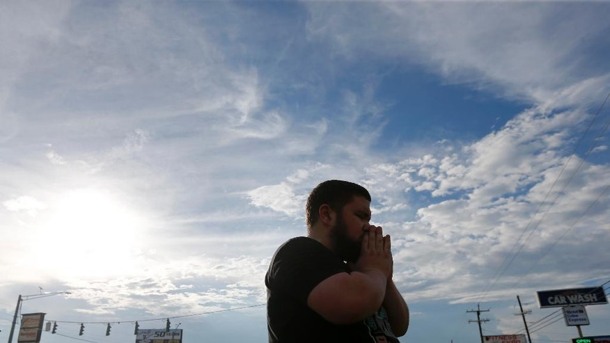 Samuel Mironchuk prays at a makeshift memorial at the scene of the shooting of police officers, in Baton Rouge, Monday, July 18, 2016. Multiple police officers were killed and wounded Sunday morning in a shooting near a gas station in Baton Rouge, less than two weeks after a black man was shot and killed by police here, sparking nightly protests across the city. (AP Photo/Gerald Herbert)