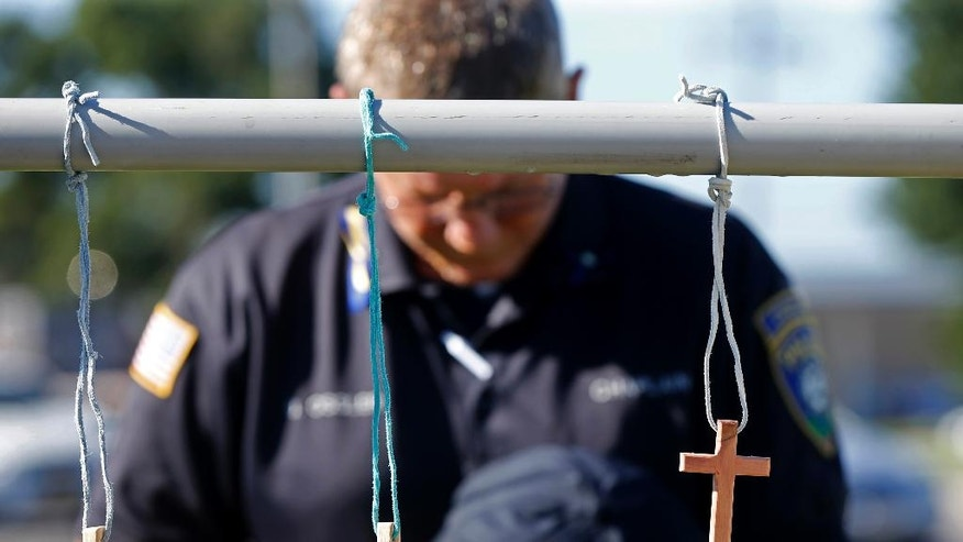 Millville, N.J. police chaplain Robert Ossler prays Monday, July 18, 2016, at a makeshift memorial at the fatal shooting scene in Baton Rouge, La., where several law enforcement officers were killed on Sunday. A former Marine set out to ambush police in Baton Rouge, authorities said Monday. (AP Photo/Gerald Herbert)