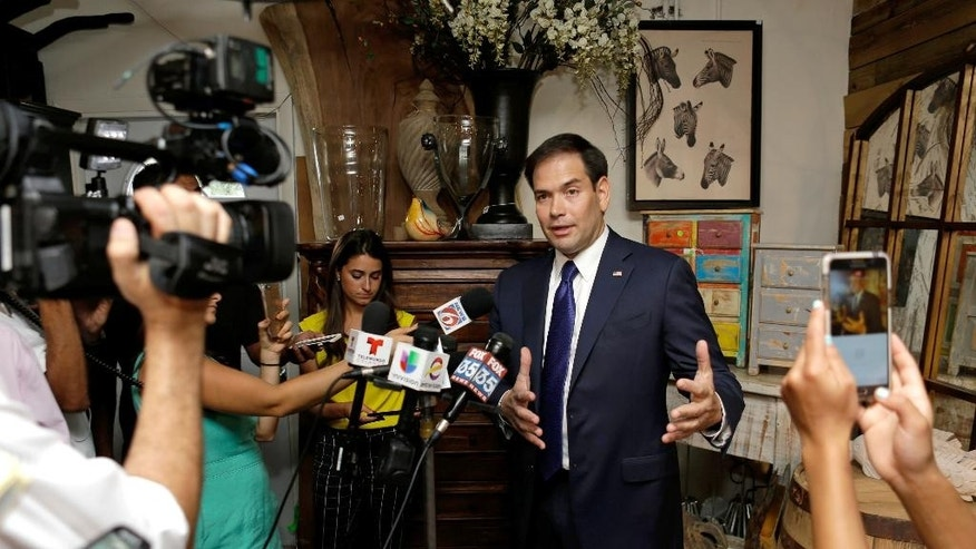 Sen. Marco Rubio, R-Fla., center, answers questions at a news conference Tuesday, July 19, 2016, in Orlando, Fla. Rubio visited several businesses that suffered significant losses due to last month's attack on the Pulse nightclub. (AP Photo/John Raoux)