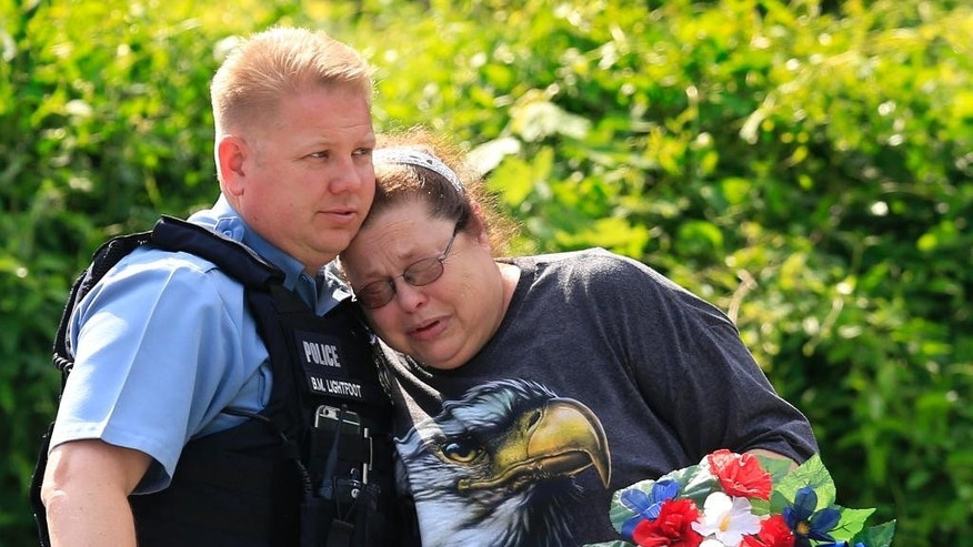 Kansas City, Kan., police officer Brad Lightfoot, left, consuls Susan Goble at the shooting scene of a police officer in Kansas City, Kan., Tuesday, July 19, 2016. Goble knows the family of the fallen officer and hoped to place a wreath near the site of the shooting.  A suspect in a drive-by shooting fatally shot Capt. Robert Melton, a 17-year veteran of the Kansas City, Kan., Police Department, on Tuesday as the officer was sitting in his patrol car, police said. (AP Photo/Orlin Wagner)