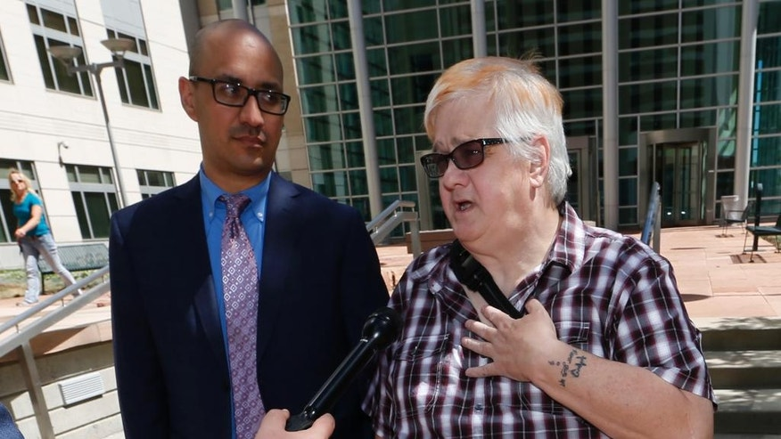Dana Zzyym, of Fort Collins, Colo., right, talks about the arguments in a hearing on Zzyym's lawsuit requiring people to pick a gender to get a passport outside the U.S. Federal Courthouse early Wednesday, July 20, 2016, in Denver. Zzyym, who was born with ambiguous sex characteristics, claims that requiring people to designate their sex to get a passport is discriminatory. Zzyym's attorney, Paul D. Castillo, from the south-central regional office of Lambda Legal in Dallas, looks on. (AP Photo/David Zalubowski)