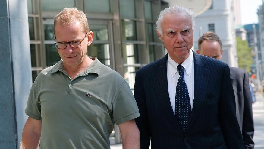 HSBC Bank's head of foreign exchange cash trading Mark Johnson, 50, left, leaves U.S. District Court in Brooklyn with an attorney after posting bail, Wednesday, July 20, 2016, in New York. U.S. Attorney U.S. Attorney Robert Capers says Johnson put personal and company profits ahead of his customers' needs by trading ahead of his customers to make millions of dollars. Johnson, a British citizen and U.S. resident was arrested Tuesday night at Kennedy Airport. (AP Photo/Kathy Willens)