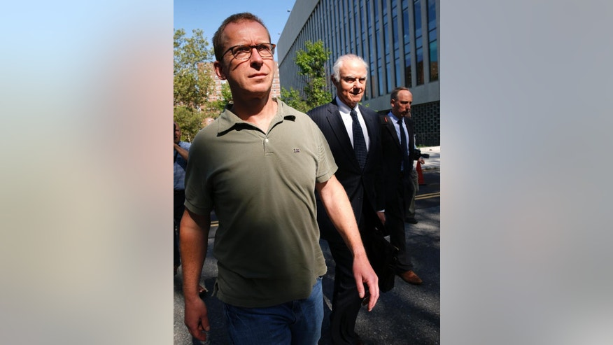 HSBC Bank's head of foreign exchange cash trading Mark Johnson, 50, left, leaves U.S. District Court in Brooklyn with an attorney after posting bail, Wednesday, July 20, 2016, in New York. U.S. Attorney Robert Capers says Johnson put personal and company profits ahead of his customers' needs by trading ahead of his customers to make millions of dollars. Johnson, a British citizen and U.S. resident was arrested Tuesday night, July 19, at Kennedy Airport. (AP Photo/Kathy Willens)