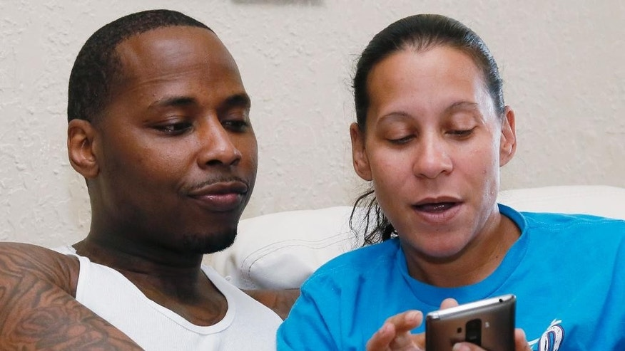 Salaam Moore, left, looks at a page his fiancee, Lola Gaines, right, shows him on her phone at their home in Oklahoma City, Wednesday, July 20, 2016. Moore was convicted of murder in 2001, and sentenced to life in prison without the possibility of parole, but the case was dismissed, all charges vacated, and he was released Monday, July 18, 2016. (AP Photo/Sue Ogrocki)
