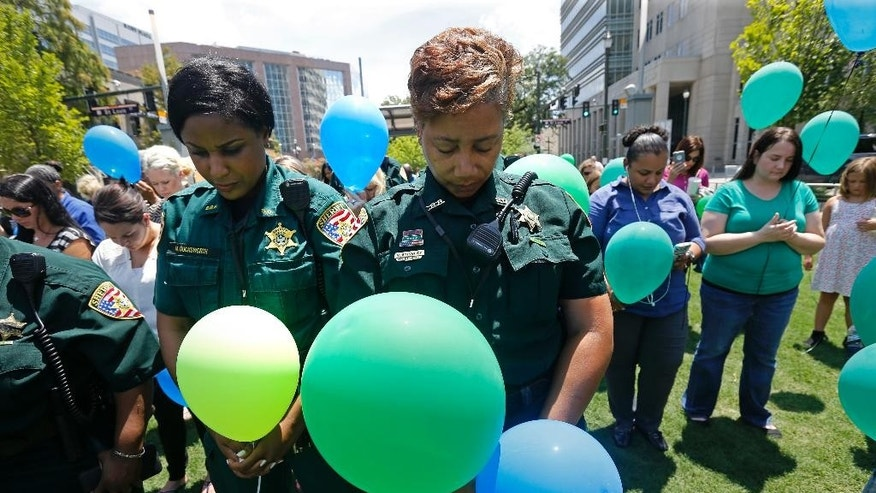 East Baton Rouge Sheriff's deputies Natasha Stingley, right, and Minnie Ducksworth, left, bow their heads in prayer before releasing balloons at a noon vigil organized by municipal court workers in downtown Baton Rouge, La., Wednesday, July 20, 2016, in honor of recent slain and injured sheriff deputies and police. Several police officers and sheriff deputies were killed and wounded Sunday morning in a shooting near a gas station in Baton Rouge, less than two weeks after a black man was shot and killed by police here, sparking nightly protests across the city. (AP Photo/Gerald Herbert)
