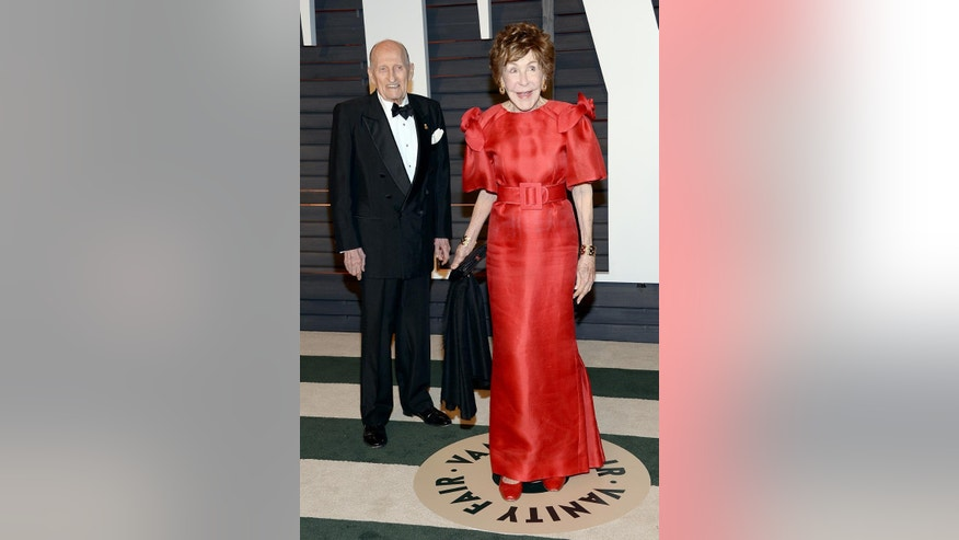 FILE - In this Feb. 22, 2015 file photo, Betsy Bloomingdale, right, and a guest arrive at the 2015 Vanity Fair Oscar Party in Beverly Hills, Calif. Bloomingdale, the widow of a department store heir who hobnobbed with the world's elite and was best friends with Nancy Reagan, has died. She was 93. Her daughter-in-law says Bloomingdale died Tuesday, July 19, 2016, at her Los Angeles home from congestive heart failure. (Photo by Evan Agostini/Invision/AP, File)