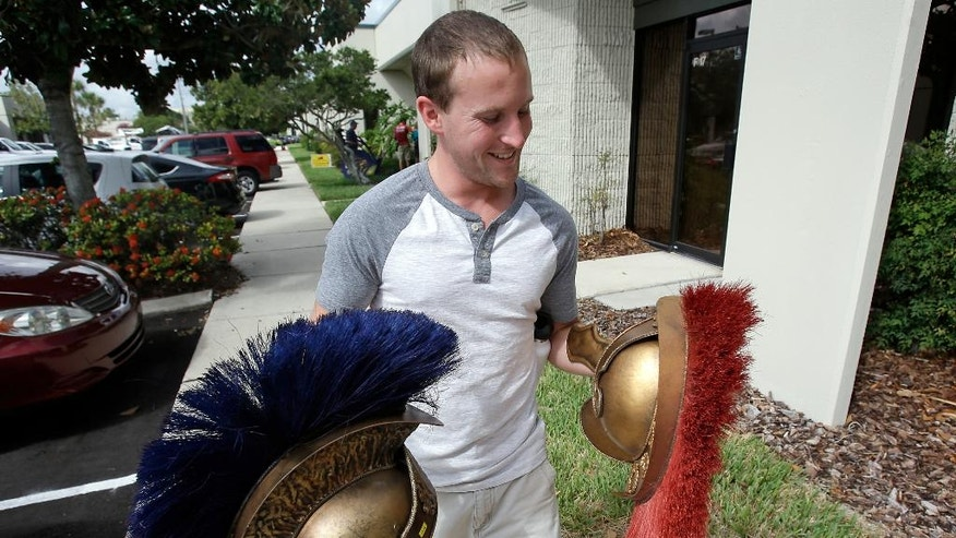 Max Donahoe leaves an estate sale from The Holy Land Experience religious theme park after he purchased two replica Roman soldier helmets, Thursday, July 21, 2016, in Orlando, Fla. The Christian theme park is holding the sale amid declining revenue and contributions. The sale starts Thursday and lasts through Saturday. (AP Photo/John Raoux)