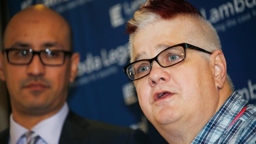 FILE - In this Oct. 26, 2015 file photo, Dana Zzyym, right, the plaintiff in a federal discrimination lawsuit filed by Lambda Legal against the U.S. State Department seeking more gender options for passports, speaks next to Paul D. Castillo, staff attorney in the South Central Regional Office of Lambda Legal in Dallas, during a news conference in Denver. A federal judge in Denver is set to hear arguments Wednesday, July 20, 2016, to consider whether the U.S. government should require people to pick a gender to get a passport. (AP Photo/David Zalubowski, file)