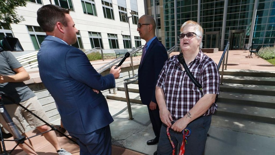 Dana Zzyym, of Fort Collins, Colo., right, looks on after arguments in a hearing on Zzyym's lawsuit requiring people to pick a gender to get a passport outside the U.S. Federal Courthouse early Wednesday, July 20, 2016, in Denver. Zzyym, who was born with ambiguous sex characteristics, claims that requiring people to designate their sex to get a passport is discriminatory. Zzyym's attorney, Paul D. Castillo, left, from the south-central regional office of Lambda Legal in Dallas, talks to a reporter as Zzyym waits. (AP Photo/David Zalubowski)