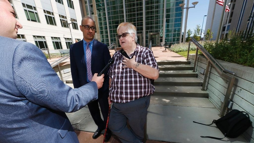 Dana Zzyym, of Fort Collins, Colo., right, talks about the arguments in a hearing on Zzyym's lawsuit requiring people to pick a gender to get a passport outside the U.S. Federal Courthouse early Wednesday, July 20, 2016 in Denver. Zzyym, who was born with ambiguous sex characteristics, claims that requiring people to designate their sex to get a passport is discriminatory. Zzyym's attorney, Paul D. Castillo, staff attorney of the south-central regional office of Lambda Legal in Dallas, center, looks on. (AP Photo/David Zalubowski)