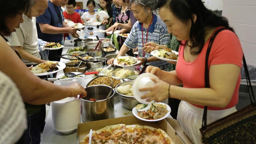 In this Sunday, June 26, 2016 photo, church-goers at the Norwich Chinese Christian Church in Norwich, Conn., participate in a potluck dinner following a Sunday service at the church. A Chinese immigrant community has been growing for more than a decade in Connecticut around two of the nation's largest casinos. Many have been drawn by good-paying jobs and a quieter life. (AP Photo/Steven Senne)