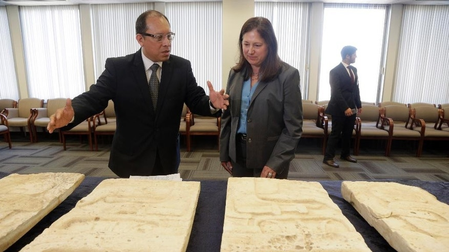 Los Angeles-based Consul General of Guatemala, Roberto Archila, left, and FBI Assistant Director in Charge, Deirdre Fike, middle, review pre-Columbian Mayan artifacts during a repatriation ceremony at the FBI offices in Los Angeles, Friday, July 22, 2016. The items came to the attention of the FBI's Art Crime Team earlier this year when an individual managing the art collection of the owner made contact. The individual could not determine the date the items were brought to the United States and elected to transfer custody of the artifacts to the FBI for repatriation to the Republic of Guatemala. The U.S. signed the 1970 UNESCO Convention addressing the illicit trafficking of cultural property around the world. (AP Photo/Nick Ut)