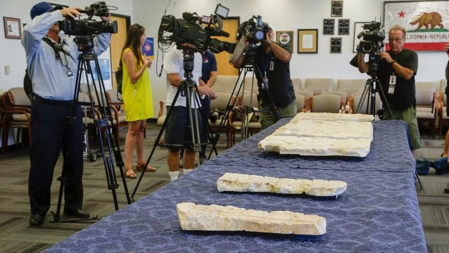 Members of the media document pre-Columbian Mayan artifacts during a repatriation ceremony at the FBI offices in Los Angeles, Friday, July 22, 2016. The Mayan artifacts were purchased innocently in the United States in the 1970s by a collector unaware the party selling them dealt in looted antiquities. Guatemala plans to display them in a museum. (AP Photo/Nick Ut)