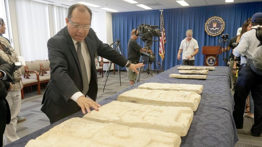 Los Angeles-based Consul General of Guatemala, Roberto Archila reviews pre-Columbian Mayan artifacts during a repatriation ceremony at the FBI Offices in Los Angeles, Friday, July 22, 2016. The ancient cultural artifacts were purchased innocently in the United States in the 1970s by a collector unaware the party selling them dealt in looted antiquities. Guatemala plans to display them in a museum. (AP Photo/Nick Ut)