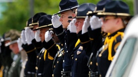 Members of a police honor guard raise their hands in salute as the casket of Baton Rouge police officer Matthew Gerald exits the Healing Place Church after funeral services in Baton Rouge, La., Friday, July 22, 2016. Multiple police officers were killed and wounded Sunday morning in a shooting near a gas station in Baton Rouge, less than two weeks after a black man was shot and killed by police here, sparking nightly protests across the city. (AP Photo/Gerald Herbert)