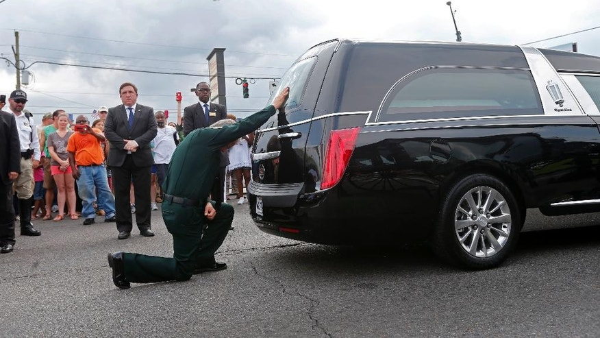 East Baton Rouge Sheriff Sid J. Gautreaux, III kneels and places his hand on the casket of deputy Brad Garafola, after it was transferred from carriage to hearse, at the scene where Garafola and two Baton Rouge police were killed, in Baton Rouge, La., Saturday, July 23, 2016. Several other officers and deputies were injured in the attack. (AP Photo/Gerald Herbert)