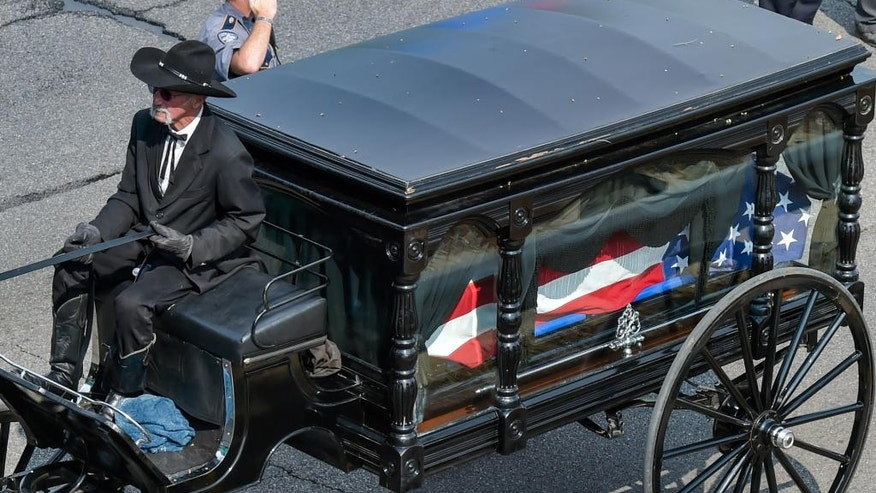 A horse drawn carriage pulls the casket of slain East Baton Rouge Sheriff Deputy Brad Garafola Saturday, July 23, 2016. Garafola and two Baton Rouge police officers were killed outside a convenience store less than a mile from police headquarters. (Scott Clause/The Daily Advertiser via AP)