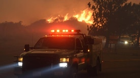 A fast burning wildfire chases down a couple of engines down Sand Caynon, near the Bear Divide in the Angeles National Forest, Calif.,  Saturday, July 23, 2016. Hundreds of county and Angeles National Forest firefighters battled the blaze, aided by three dozen water-dropping helicopters and retardant-dropping airplanes. The fire erupted Friday afternoon in the Sand Canyon area of suburban Santa Clarita near State Route 14 as the region was gripped by high heat and very low humidity. Winds pushed it into the adjacent Angeles National Forest. (AP Photo/Ryan Babroff)