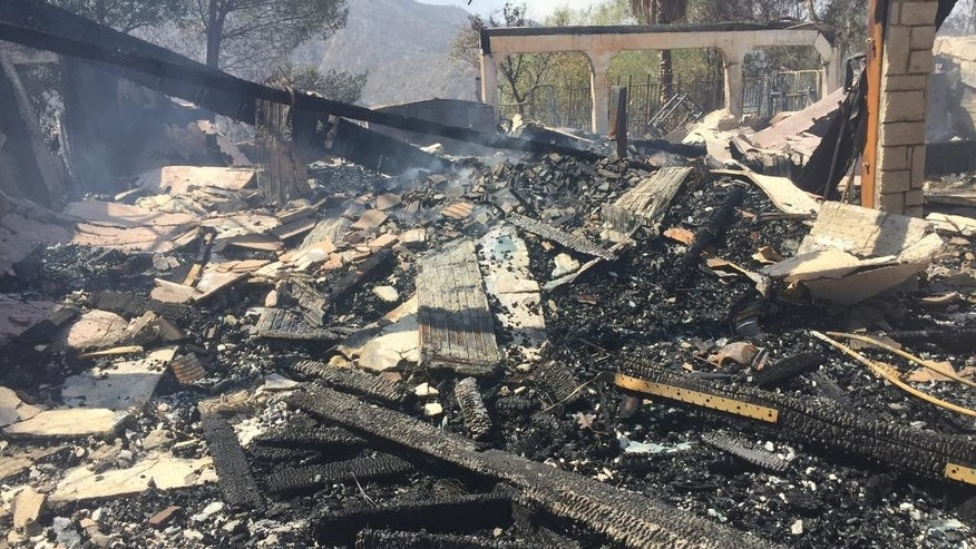 The remains of a burned home smoulder in Iron Canyon Road area near Santa Clarita, Calif., on Sunday, July 24, 2016. Two massive wildfires raged in tinder-dry California hills and canyons Sunday, leaving thousands of homes evacuated and authorities to investigate a burned body found in a neighborhood swept by flames. Firefighters have been trying to beat back a fire since Friday that has blackened more than 34 square miles of brush on ridgelines near the city of Santa Clarita and the Angeles National Forest. (AP Photo/Matt Hartman)