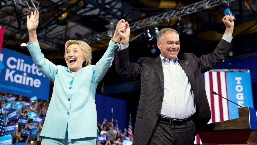 Democratic presidential candidate Hillary Clinton stands together with Sen. Tim Kaine, D-Va., during a rally at Florida International University Panther Arena in Miami, Saturday, July 23, 2016. Clinton has chosen Kaine to be her running mate. (AP Photo/Andrew Harnik)