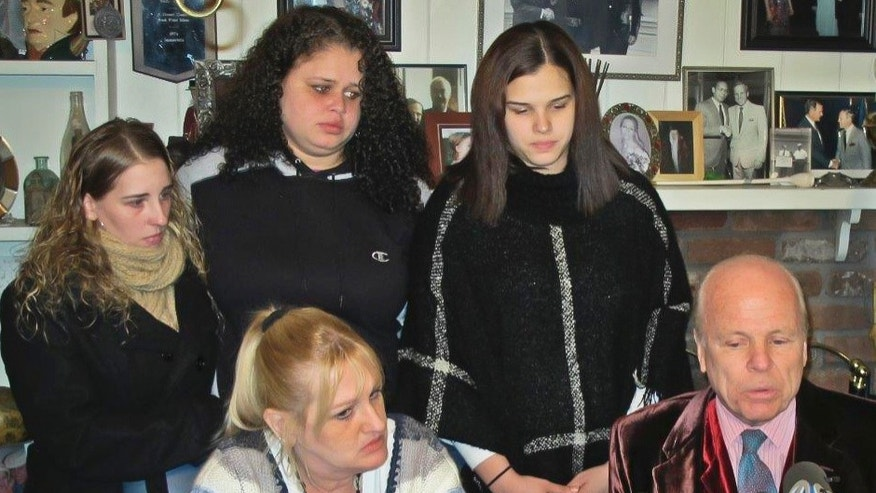 FILE - In this Friday Feb. 12, 2016 photo, Sarra Elizabeth Gilbert, center, is shown standing between her sisters Stevie Smith, left, and Sherre Gilbert, right, as her mother Mari Gilbert, seated left, and attorney John Ray, seated right, hold a press conference about Shannan Gilbert, a Jersey City, N.J., prostitute whose remains led to the discovery of 10 sets of human remains strewn along Long Island's Gilgo Beach. Police say Mari Gilbert was found dead in her apartment Saturday, July 23, 2016, and  Sarra Gilbert has been charged in the death of her mother. (AP Photo/Frank Eltman, File)