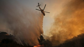A helicopter maks a drop on a wildfire near Placenta Caynon Road in Santa Clarita, Calif., Sunday, July 24, 2016. Thousands of homes remained evacuated Sunday as two massive wildfires raged in tinder-dry California hills and canyons. (AP Photo/Ringo H.W. Chiu)