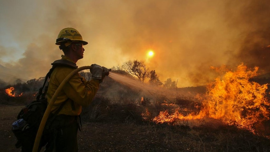 A firefighter battles a wildfire near Placenta Canyon Road in Santa Clarita, Calif., Sunday, July 24, 2016. Thousands of homes remained evacuated Sunday as two massive wildfires raged in tinder-dry California hills and canyons. (AP Photo/Ringo H.W. Chiu)