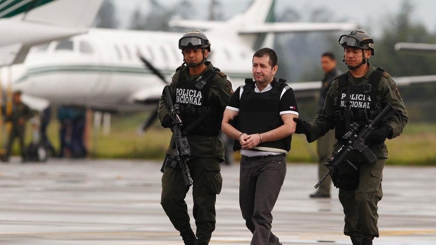 "FILE - In this Tuesday July 9, 2013 file photo, Daniel Barrera, center, is escorted by police to a waiting car prior to his extradition to the U.S. from the counter-narcotics base in Bogota, Colombia. Known as ""El Loco,"" Spanish for ""The Madman,"" Barrera is scheduled to be sentenced Mondauy, July 25, 2016, and faces a mandatory minimum of 10 years in prison and up to life after pleading guilty to a drug trafficking charge. (AP Photo/Fernando Vergara, File)"
