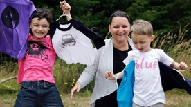In this Thursday, July 7, 2016, photo, Martine Zoer poses for a photo with her sons Tyler, 8, left, and Tristan, 5, as they wear and display some of the gender-neutral clothing she creates, in Mill Creek, Wash. Zoer founded Quirkie Kids two years ago that marketed unisex pink shirts online, starting the business after her sons wanted to wear pink but she couldn't find anything in the boys' section. Her collection has since expanded to other colors, and she set up two Instagram accounts @stillagirl and @stillaboy that share such images of boys clutching flowers or girls playing with a toy car. (AP Photo/Elaine Thompson)