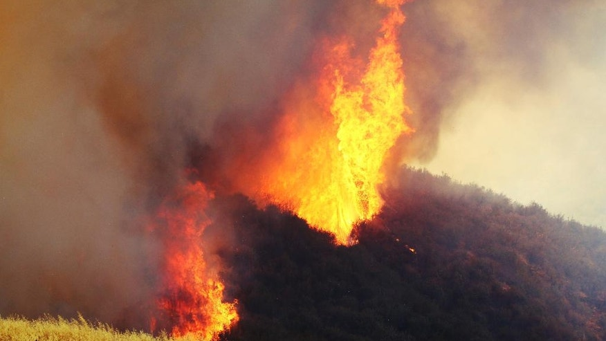 "A wildfire in northern Los Angeles County gains ferocious new power two days after it broke out in Placenta Caynon Road in Santa Clarita, Calif., Sunday, July 24, 2016. Flames raced down a steep hillside ""like a freight train,"" leaving smoldering remains of homes and forcing thousands to flee the wildfire churning through tinder-dry canyons in Southern California, authorities said Sunday. (AP Photo/Matt Hartman)"