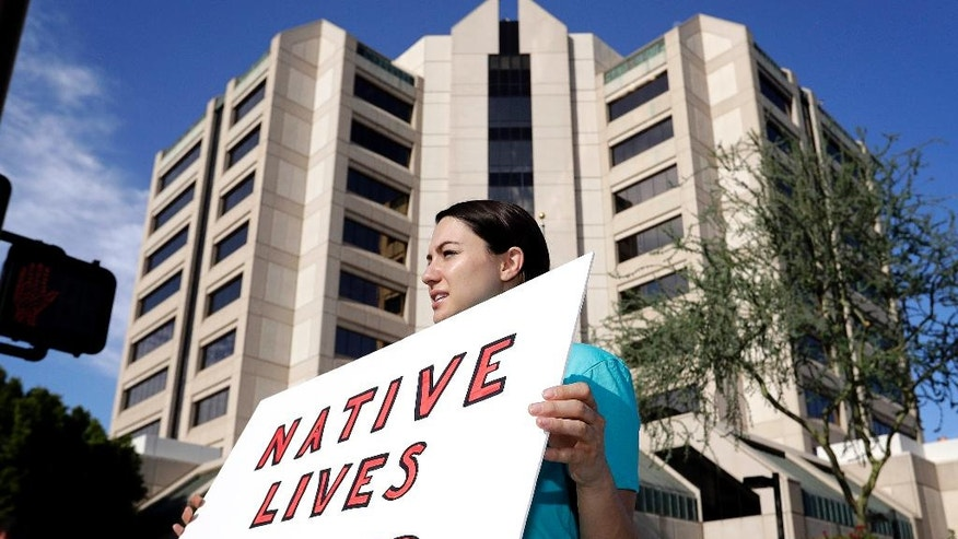 "Heather Hamel protests outside Maricopa County Attorney Bill Montgomery's office, Monday, July 25, 2016, in Phoenix. No charges will be filed against a Winslow, Ariz. police officer in the shooting death of a woman four months ago, authorities announced Friday. Maricopa County Attorney Bill Montgomery announced his office ""found no evidence of criminal conduct"" on the part of Officer Austin Shipley ""after a careful review of the facts surrounding this case including available video evidence and witness statements."" (AP Photo/Matt York)"