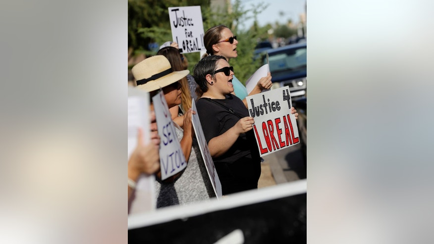 "Protesters stand outside Maricopa County Attorney Bill Montgomery's office, Monday, July 25, 2016 in Phoenix. No charges will be filed against a Winslow, Ariz. police officer in the shooting death of a woman four months ago, authorities announced Friday. Maricopa County Attorney Bill Montgomery announced his office ""found no evidence of criminal conduct"" on the part of Officer Austin Shipley ""after a careful review of the facts surrounding this case including available video evidence and witness statements."" (AP Photo/Matt York)"