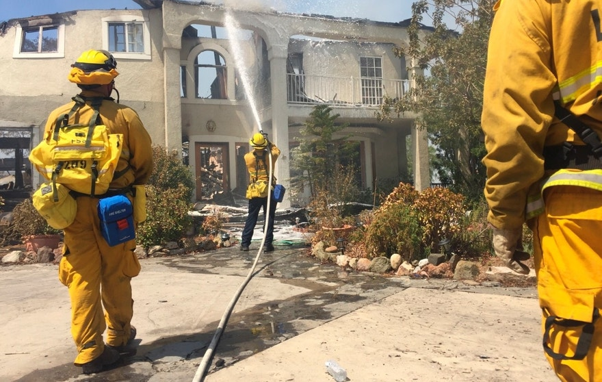 Firefighters use foam to put out flare ups on a home at the end of Iron Canyon in Santa Clarita, Calif., on Sunday, July 24, 2016. Authorities say 18 homes have been destroyed and an additional 1,500 are threatened as crews battle a massive wildfire in wooded canyons north of Los Angeles. The blaze has blackened more than 34 square miles of dry brush withered by days of triple-digit heat on the edge of the Angeles National Forest. It was just 10 percent contained Sunday. (Katharine Lotze/The Santa Clarita Valley Signal via AP)