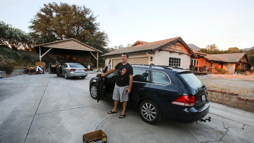 Resident Laurent Lacore, 48, returns to his home near Sand Canyon Road in Santa Clarita, Calif., Monday, July 25, 2016. The majority of some 20,000 people forced from their homes by a wildfire that exploded during the weekend were told they could return home Monday night, though an army of firefighters continued battling flames in the rugged hills and canyons northwest of Los Angeles. (AP Photo/Ringo H.W. Chiu)