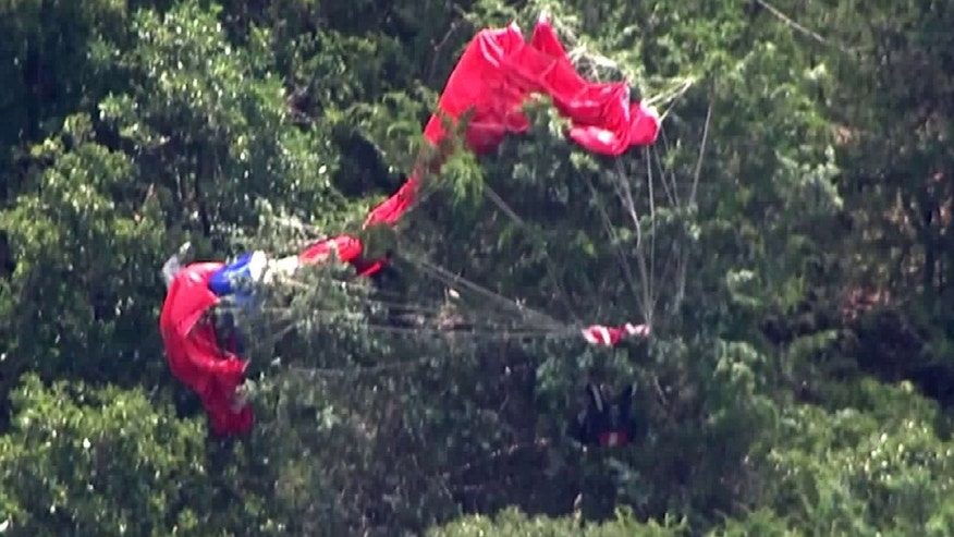 This image from video provided by KFOR-TV in Oklahoma City shows a parachute caught in a wooded area Monday, July 25, 2016, near Cushing, Okla.