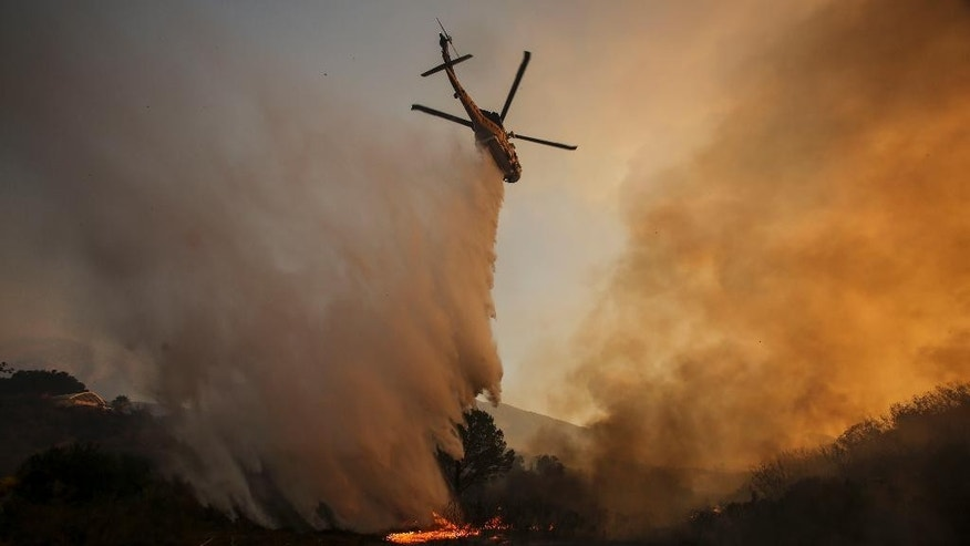 FILE- In this Sunday, July 24, 2016 file photo, a helicopter makes a drop on a wildfire near Placerita Canyon Road in Santa Clarita, Calif. The smoky fire tore through drought-ravaged brush that hadn't burned in decades amid a sweltering heat wave and exploded over the weekend.  (AP Photo/Ringo H.W. Chiu/File)