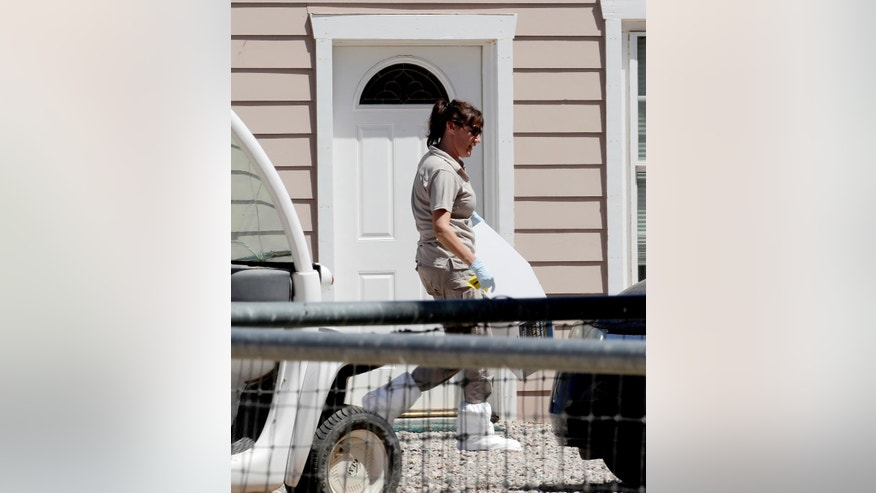A crime scene investigator works outside a home where multiple bodies were found, Tuesday, July 26, 2016, in Gilbert, Ariz. Sheriff's officials say multiple dead bodies have been found inside a home in an unincorporated area of Gilbert, east of Phoenix. There's no immediate word Tuesday on how many bodies or their ages or genders. (AP Photo/Matt York)