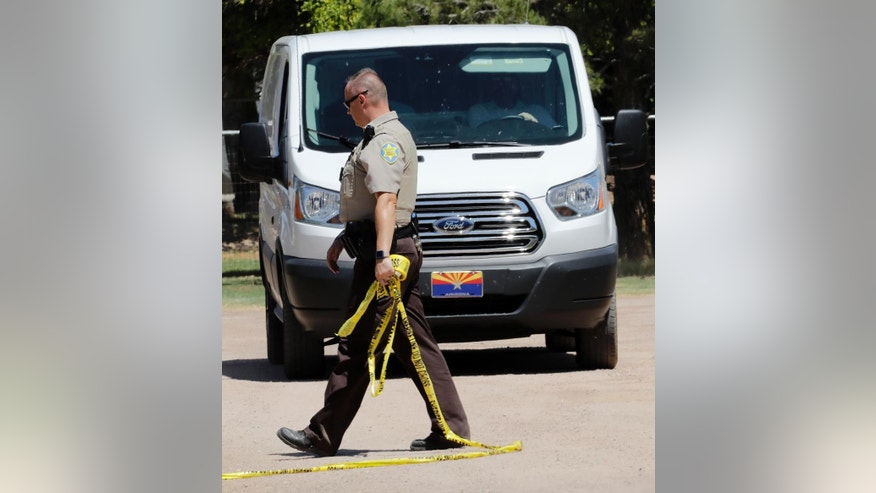 A Maricopa County Sheriffs Deputy lets a crime scene van past the police tape outside a home where multiple bodies were found, Tuesday, July 26, 2016, in Gilbert, Ariz. Sheriff's officials say multiple dead bodies have been found inside a home in an unincorporated area of Gilbert, east of Phoenix. There's no immediate word Tuesday on how many bodies or their ages or genders. (AP Photo/Matt York)