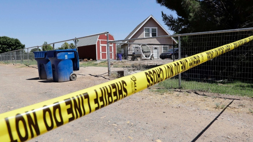 Crime scene tape blocks the entrance to a home where multiple bodies were found, Tuesday, July 26, 2016, in Gilbert, Ariz.