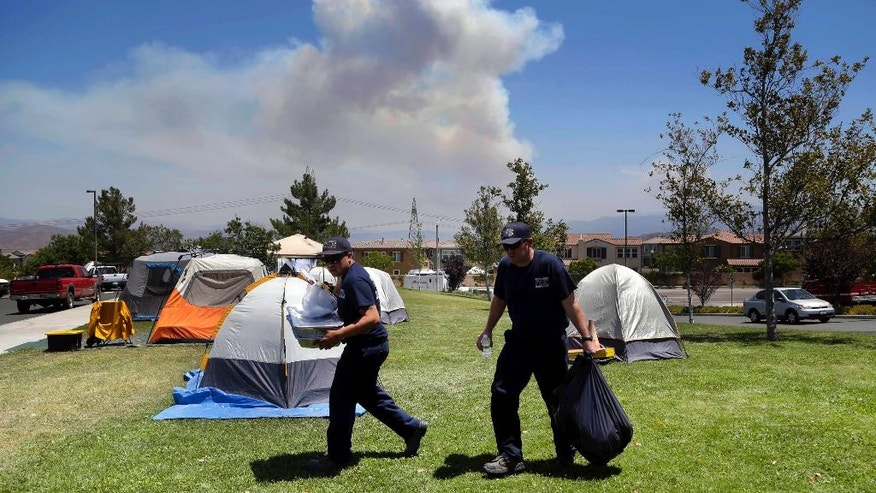 In this Tuesday, July 26, 2016 photo, firefighters carry food and supplies past dozens of firefighter tents covering a field at a firefighter operations base camp that has been established at Golden Valley High School in Santa Clarita, Calif., as smoke from the Sand fire looms up in the background. When a wildfire becomes too big for local departments to handle alone, an incident command network is activated to to coordinate the large numbers of people, equipment and supplies needed for these operational bases. (AP Photo/Nick Ut)