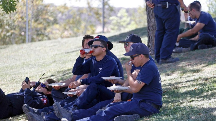 In this Tuesday, July 26, 2016 photo, firefighters eat and rest at a firefighter operations base camp that has been established at Golden Valley High School in Santa Clarita, Calif. When a wildfire becomes too big for local departments to handle alone, an incident command network is activated to to coordinate the large numbers of people, equipment and supplies needed for these operational bases. (AP Photo/Nick Ut)